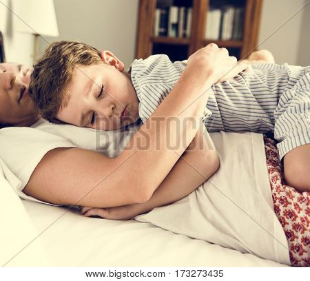 Family sleeping on the bed togetherness