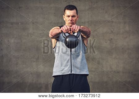 Expressive Man Holding Hands Up With Kettlebell