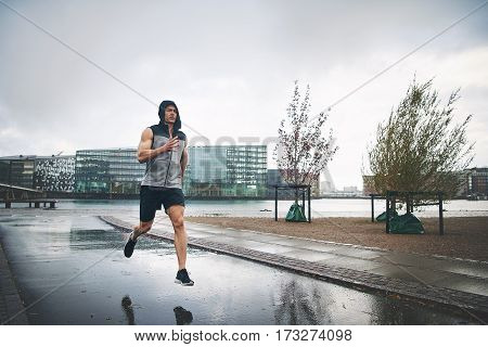 Young Man Running In Rain On Street