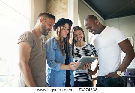Four Young People Watching Something On Tablet