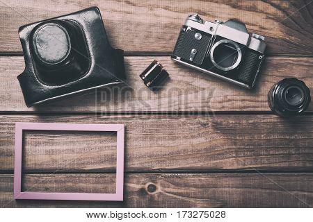 Old film camera with lens case photo frame and film on wooden background. Vintage toned and top view.