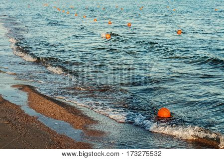 Sea with waves floats a lot of protective buoys.