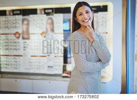 Single beautiful happy young white woman in striped shirt with fingers under chin in eye wear shop
