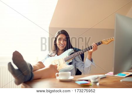 Cute Young Woman With Guitar And Feet On Table