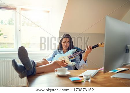 Cute Woman Playing Guitar In Front Of Computer