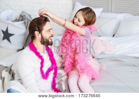 Girl party. Positive delighted bearded male person sitting near his daughter in the bedroom wearing white jumper and pink shawl, looking at his daughter