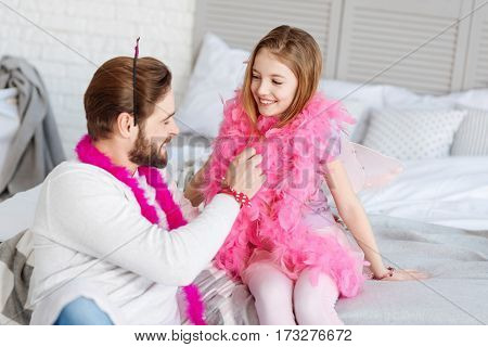 Love you dad. Joyful smiling girl wearing costume for princess keeping hands on the bed turning head to her daddy