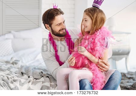Pleasure time. Attractive girl having smile on her face wearing pink feather shawl and violet crown sitting on the knees of her father