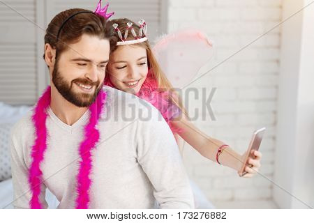 Selfie time. Portrait of happy father and daughter wearing costumes for masquerade spending time with pleasure while using phone for shooting