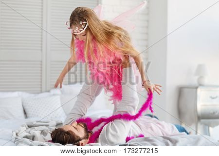 Can fly. Strong bearded brunette lying on the bad holding his daughter over himself while playing