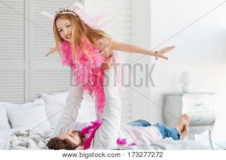 I am fairy. Positive girl wearing pink wings and feather shawl stretching her arms while posing on camera