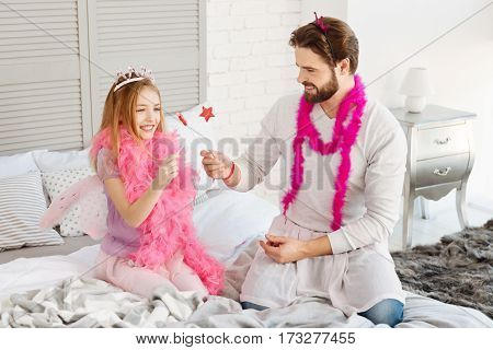 Magic sticks. Pretty smiling girl wearing pink feather shawl and wings holding lollypop in right hand while looking at this