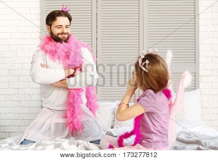 Stay in one pose. Happy father wearing pink feather shawl and skirt standing on his knees while looking at his daughter