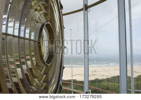 An up close view of the light of a lighthouse from inside the tower with a view of the ocean in the background.