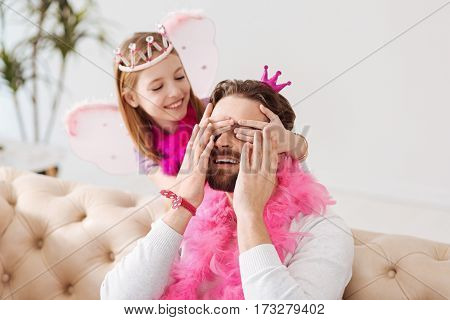 Play hide-and-seek. Funny daughter wearing pink feather around her neck keeping her hands on eyes of her father while looking at him