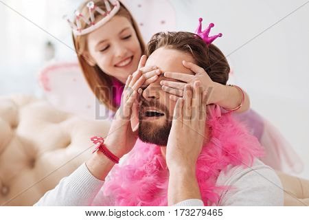 Where are you. Young bearded male wearing pink feather around his neck keeping his mouth opened putting his hands on hands of his daughter