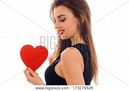 Beautiful girl stands sideways and holds a red Valentine heart close up isolated on white background.