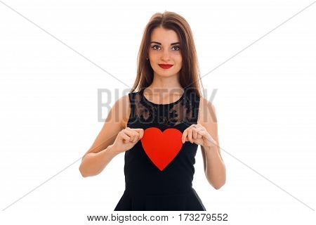 Cute young girl in black dress holding a red heart isolated on white background.