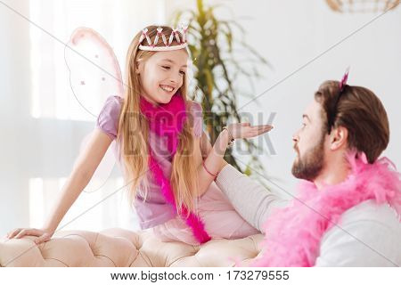 My advice. Amazing little girl wearing wings and pink feather around her neck keeping her right hand on the back of sofa while looking at daddy