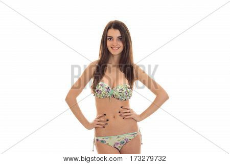 Young attractive girl in bathing suit holding hands on her hips and smiling isolated on white background