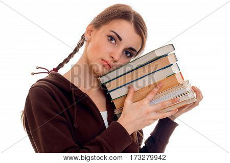 Young girl with pigtails leans her head on a stack of books isolated on a white background close up.