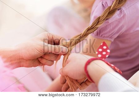 Make efforts. Picture of male hands wearing red bracelet making long braid to daughter