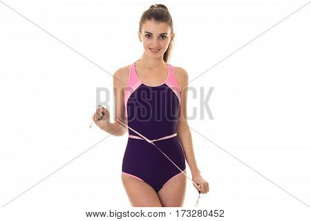 Young athletic girl in swimsuit holding a measuring tape and looking directly isolated on white background