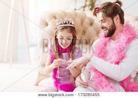 Be attentive. Positive delighted father having funny hairstyle keeping his hand near his daughter while she going to paint nails