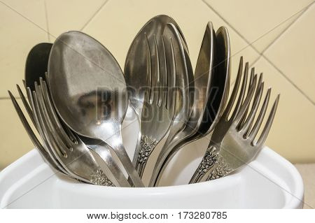 Many metal forks and spoons at home