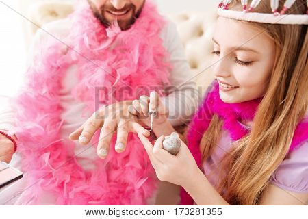 Best variant. Positive delighted girl keeping smile on her face holding brush in right hand while painting male nails
