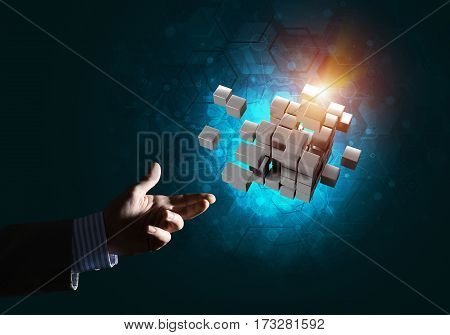 Close of businessman hand holding cube figure as symbol of innovation, mixed media