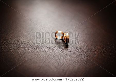 Golden Wedding Rings On Brown Leather Background On Natural Light.