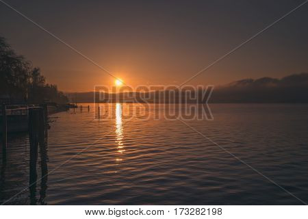 A calm orange sunset on the shore of a lake in germany, bodensee