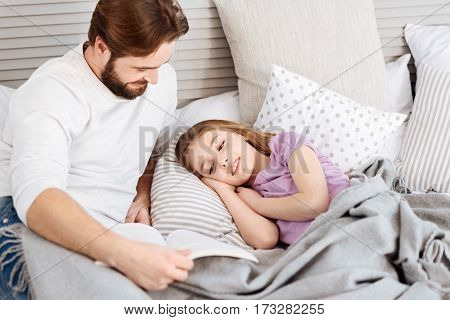 Sweet dreams. Pretty girl lying under grey blanket holding her hands under head while reading book