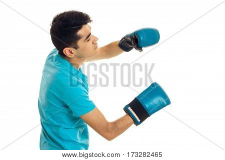 a young guy in a blue t-shirt stands sideways in boxing gloves is isolated on a white background