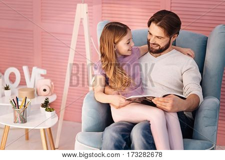 Sweet home. Handsome bearded man wearing white jumper embracing his daughter while holding book in left hand