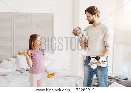 Keep fit. Sporty bearded man lifting bells standing near his daughter in semi position while showing exercises