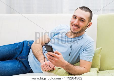Man listening music on the phone AT HIS HOME