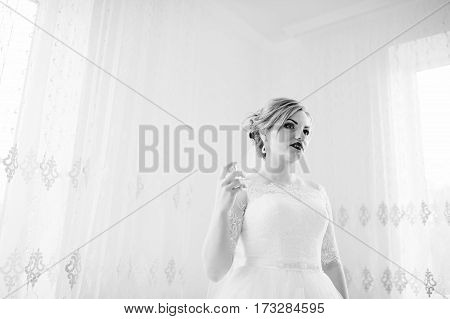 Blonde Bride On Wedding Day Near Curtains At Her Room With Parfumes At Hand. Black And White Photo