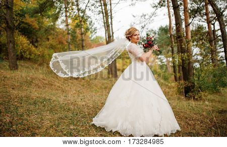 Blonde Bride With Wedding Bouquet And Bright Make Up At Autumn Pine Wood.