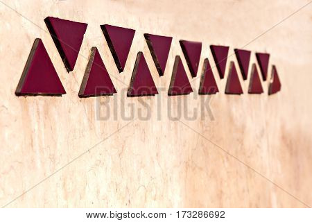 mosaics in a line of triangles on wall in perspective.