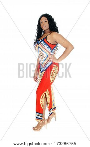 A tall lovely young African American woman standing in a long colorful dress isolated for white background with black curly hair.
