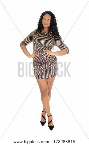 A beautiful African American woman standing in a short dress and and her legs crossed isolated for white background.
