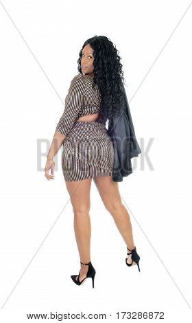 A beautiful African American woman standing in a short dress and jacket over her shoulder isolated for white background.