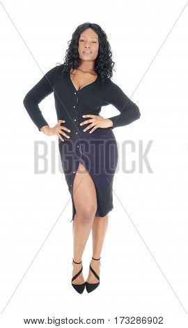 A beautiful African American woman standing in a black dress and heels isolated for white background.