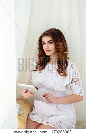 Beautiful pregnant woman is using a digital tablet while sitting on the couch at home