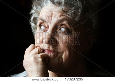 Sad looking grandmother face on a black