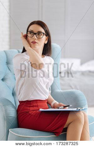 What is it. Attractive thoughtful young businesswoman sitting in the armchair and looking aside while being distracted by something