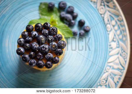 Very gentle blueberry dessert with fresh blueberries and white curd cream and shortcake dough and green mint on a blue plate.