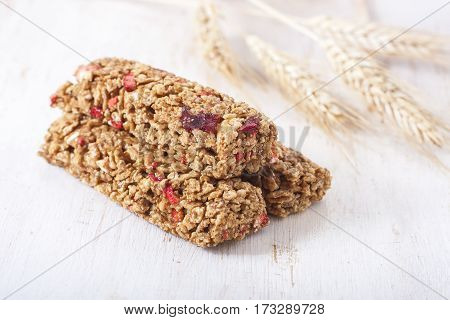Granola Bar And Wheat On Wooden Background.